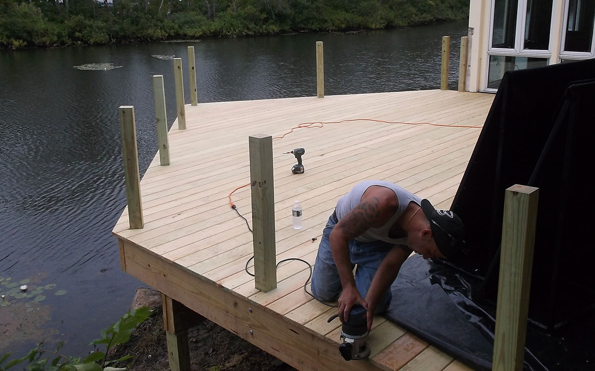 Treated wood deck (PT). Built over the water for a local restaurant. Utilizes helical piles for support. Acton, MA 01720.