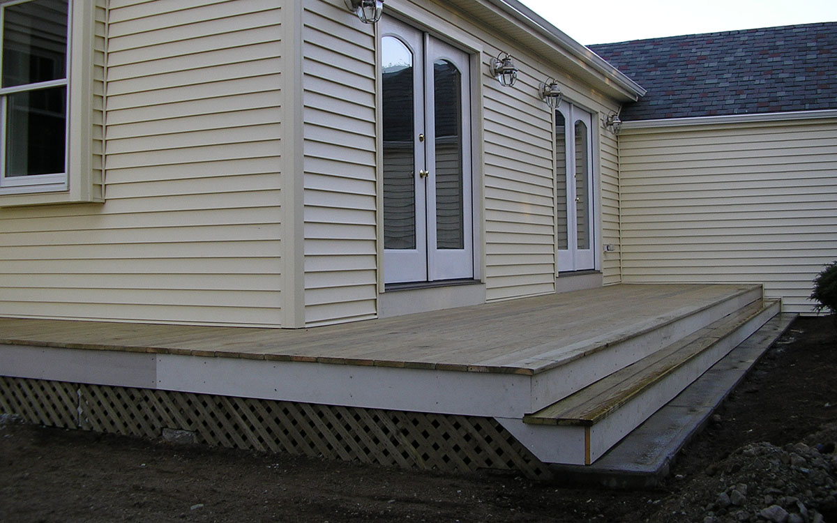 Ground level pressure treated wood deck with lattice and concrete step. Franklin, MA 02038.
